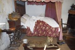 Château - Français:   Une pièce aménagée en pièce à vivre d\'antan. Devant le lit un loup naturalisé, un des derniers tué en 1904 à Augignac. - Musée des tisserands à Varaigne, Dordogne, France