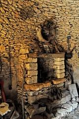 Maison d'habitation et cabanes en pierre sèche du Breuil - Deutsch: Eine Werkstatt mit Feuerstelle in einer Hütte aus Trockenmauerwerk irgendwo in Frankreich.