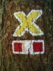 Mur païen -  le signe jaune balisant le circuit du Mur Païen.(Ce signe rappelle la Rune Gebo.)