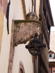 Maison Adolphe - English: A lion's head ornament holding a cogwheel in its mouth. Colmar.
