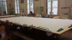 Mobilier National - Français:   Établi de tapisserie des ateliers de tapisserie des Gobelins où voit un travail mis à plat et fixé à l\'aide de poids.