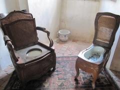 Mobilier National - Français:   Fauteuil à l\'anglaise avec sa réserve d\'eau cachée dans l\'épaisseur du dossier et bidet (Château de Villemonteix dans la Creuse)