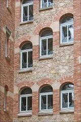 Immeuble dit Castel Béranger -  Façade intérieure en briques et en meulières donnant sur la cour intérieure (Castel Béranger)  Chaque fenêtre possède des vitraux qui ont été conçus par le maître verrier: Georges Néret.