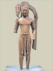 Musée Guimet - Harihara Cambodge Asram Maha Rosei, district de Prei Krabas, province de Takeo Style de Phnom Da Époque préangkorienne VIIè siècle (?). Grès. H. 173 cm.  Mission Etienne Aymonier, 1882-1883. Musée Guimet. MG 14910  Harihara est moitié Vishnu à droite sur la photo (avec tiare, disque) et moitié Shiva à gauche sur la photo (avec trident, chignon avec croissant de lune, peau de tigre)  Hari (Celui qui enlève) est un des noms de Vishnu. Celui qui enlève est aussi Celui qui nous console selon Alain Daniélou.  Hara (l\'Effaceur) est un des noms de Shiva. Il est identifié à la maladie, à la mort ainsi qu\'à la puissance destructrice qui, à la fin des temps, efface l\'Univers.   Référence: Pierre Baptiste et Thierry Zéphir, L\'art khmer dans les collections du musée Guimet, 2008, (ISBN978-2-7118-4960-4), pages 52-57.