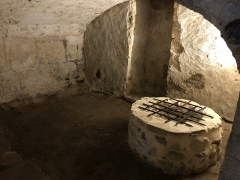 Eglise abbatiale Saint-Pierre - Français:   Salle du puits de la crypte de l\'abbatiale Saint-Pierre de Mozac, dans les deux premières chapelles de l\'ancien martyrium détruit au XVe siècle et réutilisé comme caveau des moines en 1616. Époque carolingienne. Comblée après les tremblements de terre de la moitié du XVe siècle qui ont conduit à l\'écroulement du clocher et du chevet supérieur. Redécouverte et restaurée en 1849 par l\'architecte diocésain Aymon Mallay. La margelle du puits a été édifiée par le Club historique mozacois dans les années 1990 et la grille de sécurité posée en 2018. Le puits se trouvait dans la chapelle centrale du martyrium dans l\'axe est-ouest et précisément au centre de la largeur de la crypte. Il est toujours alimenté en eau de manière naturelle par la nappe phréatique.