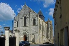 Eglise Notre-Dame - Châtillon-sur-Indre (Indre)  Eglise Notre-Dame (Ancienne collégiale Saint-Outrille).  Ensemble sud-ouest. La face occidentale avait autrefois un porche avancé.  La collégiale romane Saint-Outrille aurait été fondée au Xe ou au XIe siècle pour accueillir les reliques du saint.  L\'édifice actuel fut reconstruit dans le dernier quart du XIe siècle (chœur, abside) et se poursuit au XIIe (transept, absidioles).  Au XIIe siècle, la nef fut rehaussée et élargie par l\'adjonction de collatéraux.  L\'ensemble est roman, sauf la chapelle latérale, de style gothique comme la croisée de transept, qui fut construite au XVe siècle.  L\'église Saint-Outrille devint Notre-Dame avant la Révolution.   En 1791, elle devint église paroissiale et fut requisitionnée pour un curé constitutionnel.
