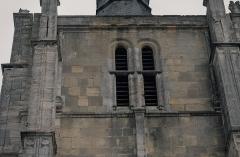 Eglise Notre-Dame - Quatrième niveau de la façade du clocher, ici côté sud. Le centre est occupé par des baies géminées, assez mince, en arc en plein cintre, avec archivoltes à base prismatique, munies de croisées à la moitié de la hauteur, et garnies d'abats-sons. Sur les côtés, contre les contreforts, apparaissent deux colonnes, posées sur des corbeaux prenant la forme de consoles, au fût qui change d'axe lorsque le contrefort devient moins grêle. Les chapiteaux sont d'un ordre hybride, ressemblant à un mélange de dorique et de chapiteau médiéval. Enfin la corniche, surmonté du garde-corps de la terrasse. Au-dessus des colonnes, la corniche arbore des consoles. L'ensemble est un mélange de pierre de Vernon et de Caen.