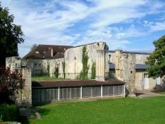 Ancienne abbaye Saint-Arnould - Français:   Emplacement du chœur de l\'abbatiale; au fond, un bâtiment du XVIIIe siècle; à droite, ruines d\'un bâtiment conventuel médiéval avec une construction moderne au premier plan.