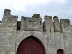 Ruines du château -  Picquigny (Somme, France) -   Château.  Partie supérieure de la Porte de la Barbacane. Les blasons décorant la façade ont été martelés. Seul celui de gauche a été partiellement préservé.   La porte charretière est en ogive, celle (plus étroite) réservée aux piétons est en plein cintre.