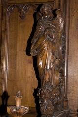 Eglise Notre-Dame - English:  Cheek choir stalls: angel holding a scroll.