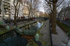 Canal Saint-Martin - The Canal Saint-Martin is a 4.5 km long canal in Paris. It connects the Canal de l\'Ourcq to the river Seine and runs underground between Bastille (Paris Métro) and République (Paris Métro).  Construction of the canal was ordered by Napoleon I in 1802, in order to create an artificial waterway for supplying Paris with fresh water to support a growing population and to help avoid diseases such as dysentery and cholera.  Gaspard de Chabrol, prefect of Paris, proposed building a canal from the Ourcq River (starting 100 km northeast of Paris). The canal was dug from 1802 to 1825, funded by a new tax on wine. The canal was also used to supply Paris with food (grain), building materials, and other goods, carried on canal boats. Two ports were created in Paris on the canal to unload the boats: the Port de l\'Arsenal and the Bassin de la Villette [Wikipedia.org]