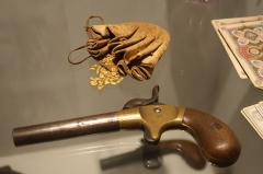 Hôtel de Fleuriau - English: 19th century leather and fluvial gold nugget purse. Small single shot game gun. Steel, brass, wood; circa 1850. Playing cards, 19th century. New World Museum, La Rochelle.
