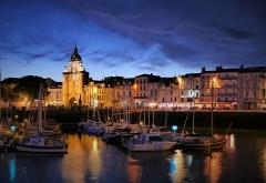 Porte de la Grosse-Horloge - Deutsch: Uhrenturm in La Rochelle mit Hafen in Abendansicht