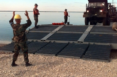 Cimetière américain et la chapelle de Meuse-Argonne - English: A sailor from Beachmaster Unit 2 guides the driver of a dump truck as he comes ashore near Paldiski, Estonia, from a lighter craft bringing equipment from the S.S. Sgt. Matej Kocak during Exercise Baltic Challenge 97, on July 14, 1997. Baltic Challenge '97 is a multinational exercise conducted as a NATO Partnership for Peace initiative involving more than 2,600 military personnel from Denmark, Estonia, Finland, Latvia, Lithuania, Norway, Sweden, and the U.S. The focus of the training is peacekeeping tasks and humanitarian assistance operations. The lighter craft are being used to move equipment off-loaded from the Maritime Prepositioning Ships anchored off shore to the exercise area on the beach. Beachmaster Unit 2 is homeported in Little Creek, Va.