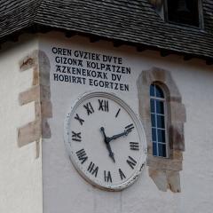 Eglise Saint-Martin -   Bell-tower clock of the Saint Martin's church in Sare.  Inscription in Basque: Oren guziek dute gizona kolpatzen azkenekoak du hobirat egortzen, every hour hurts the man, the last one sends him to the grave.