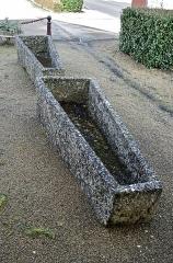 Eglise Saint-Etienne - Paulnay (Indre)  Sarcophages sur le parvis de l'église Saint-Etienne.    Des travaux d'adduction d'eau en 1972, ont amené la découverte de sarcophages au coeur du village. Des fouilles de sauvetage ont été entreprises au début des années 80. Lors de fouilles, les assises d'un temple gallo-romain du IIème siècle ont été dégagées, ainsi que des inhumations dont les plus anciennes dateraient de l'époque mérovingienne comme en témoignent les deux sarcophages exposés sur le parvis.   Voir: Girault Jean-Louis. Fouille de sauvetage sur un cimetière mérovingien à Paulnay (Indre). In: Revue archéologique du Centre de la France, tome 28, fascicule 1, 1989. pp. 107-108