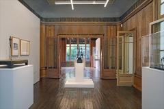 """Immeuble - Au fond, dans la salle côté rue, les oeuvres: """"la Nuit"""" et """"Figurine entre deux maisons""""; au premier plan dans la salle traversante, """"les places""""  L'œuvre la plus célèbre de Giacometti, l'Homme qui marche, plus qu'un chef- d'œuvre, est une icône de l'art du XXe siècle. Cette exposition réunit pour la première fois les différents modèles grandeur nature, ainsi que la plupart des variations sculptées et dessinées. Accompagnée de nombreux documents et dessins inédits, elle retrace la généalogie du motif, depuis la Femme qui marche de la période surréaliste, jusqu'aux icônes créées en 1959-1960...  Extrait du site de l'exposition """"L'Homme qui marche.  Une icône de l'art du XXème siècle"""" à l'Institut Giacometti, Paris  <a href="""