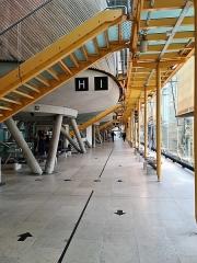 Palais de Justice -  La salle des pas perdus du Tribunal Judiciaire de Bordeaux est abritée par un parallélépipède de verre et d'acier. Les salles d'audience sont des coques de bois en lévitation sur des coupelles de béton sur pilotis. On y accède par des passerelles métalliques jaunes.