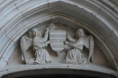 Chapelle Notre-Dame ou Miraculeuse ou de la Vierge - Français:   Tympan de l\'entrée de la Chapelle Notre-Dame (Classé). Deux anges supportant un blason «azur à quatre fasces d\'argent et un besant de même» et avec une mitre en cimier.