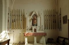Eglise Saint-Symphorien - Billy (Loir-et-Cher)  Eglise Saint-Symphorien. La chapelle sud.  La nef, la partie la plus ancienne, construite en petit appareil, a été édifiée au XIe siècle. Le clocher, tour carrée sur la façade sud, a été rajouté au XIIIe siècle; l'accès à l'étage se fait par une tourelle externe avec un escalier à vis. Le choeur et l'abside seront reconstruit à la fin du XVe siècle. Les vantaux du portail seraient du XVIe siècle, le portail sera refait dans la seconde moitié du XIXe siècle. Des chapelles latérales, formant transept, sont ajoutées au XXe siècle. Une porte méridionale* a été murée.  Des petits personnages sont sculptés sur la façade occidentale, au dessus du portail.  A l'intérieur, sur le mur nord, un fragment de peintures murales, du XVe siècle, subsiste. De gauche à droite:  Saint Blaise nu, martyrisé par deux bourreaux avec des peignes à carder. Sainte Catherine, près de la roue de son supplice, couronnée et qui tient une épée. Sainte Barbe tenant une palme et un livre, aux côtés de sa tour.  Sur le mur nord, toujours, une épitaphe, en caractères gothiques, à la mémoire du prieur Pierre de Villède, mort en 1511.  Dans la petite chapelle sud, une série de quatorze cierges de la confrérie de saint Vincent, en zinc, du XIXe siècle.    Une archive mentionne le don de l'église par Childebert Ier* au prince Vulphin* pour l'abbaye de Selles-sur-Cher.  En 1128, après qu'elle fut usurpée par des laïcs, son dernier possesseur Hugues Graflutz la remet à Jean II évêque d'Orléans qui l'attribue à l'abbaye de Selles-sur-Cher; un prieuré-cure y est alors créé.  Au 15e siècle, un prieuré existait à Billy. Sous François Ier, l'église fit partie du domaine de la couronne jusqu'à la disparition du roi.     C'est à la porte méridionale de l'église que se faisait la purgation canonique. Les juges ne pouvant établir suffisament les faits d'un crime, ordonnaient que l'accusé soit conduit à la porte méridionale de l'église pour y prêter serment, devant la p