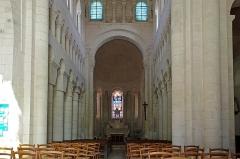 Eglise Saint-Genou (ancienne abbatiale) - Français:   Nef Abbatiale Saint-Genou de Saint-Genou. L\'église St Genou faisait partie d\'un monastère bénédictin. Elle conserve de l\'époque romane son choeur et son chevet (XIIe siècle).  La nef et les clochers, ruinés aux XVIIe siècle, ont été détruits en 1676. L\'ancienne abbatiale ne mesure plus que 23 mètres de long, alors qu\'à l\'origine, au XIIe siècle, elle en faisait 50. Les travées du choeur avec des chapiteaux sculptés et au dessus un faux triforium.  Sous l\'abside circulaire, au droit de l\'autel, le tombeau de saint Genou.   Le triforium est un passage étroit pratiqué dans l\'épaisseur du mur au-dessus des grandes arcades. Ce passage ouvre sur l\'intérieur par une série de petites arcades, et à partir de 1240 environ, il ouvre sur l\'extérieur et éclaire le haut. Le faux triforium est une arcature plaquée contre le mur au dessus des grandes arcades.