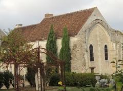 Ancien prieuré Notre-Dame-des-Marchais - Français:   Prieuré Notre-Dame-des-Marchais, reste de l\'ancienne chapelle avec sur le pignon de ce batiment haut et large couvert de tuiles, une arcade avec deux fenêtres de part et d\'autre d\'un chaînage de pierres taillées vertical dans l\'axe de l\'arcade gothique. Deux sapins filiformes sur le côté du batiment et des haies et arbustes, une pelouse et une structure métalique ainsi qu\'une vasque dans le jardin au premier plan