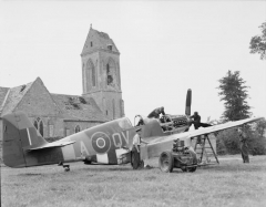 Eglise - English:   Royal Air Force- 2nd Tactical Air Force, 1943-1945.  Members of a Repair and Salvage Unit attend to North American Mustang Mark III, FZ190 \'QV-A\', of No. 19 Squadron RAF in the shadow of the shell-torn village church at B12/Ellon, Normandy.  From left to right they are: Flying Officer F H Price of Hereford, Leading Aircraftman L Polley of Boxted near Colchester, Corporal J Hughes of Crewe, Corporal N Lee of Birmingham and Sergeant W G Ward of Emsworth.