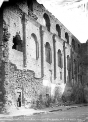 Eglise abbatiale Saint-Pierre-Saint-Paul - Ruines, intérieur : pan de mur de la nef, côté gauche, homme posant devant une porte
