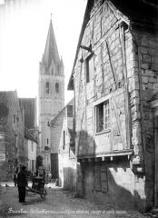 Eglise abbatiale Saint-Pierre-Saint-Paul - Clocher et vieille maison : rue animée