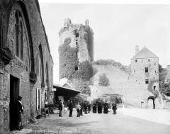 Restes du château - Donjon, côté ouest. Relais de poste à gauche avec groupe de personnes en pose devant l'omnibus à cheval Bricquebec à Carteret