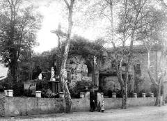 Ancien prieuré - Ancienne église : abside en ruines. Dans le jardin, reconstitution du Golgotha (Le Christ crucifié entouré des deux larrons). Devant le mur d'enceinte, groupe d'enfants