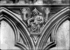 Cathédrale Saint-Pierre - Stalles, écoinçon : ange proteur de couronnes et figure symbolique des Péchés capitaux
