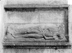 Eglise - Bas-relief sculpté dans le contrefort, à droite du portail de la façade nord : Gisant