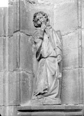 Ancienne abbaye - Portail de la façade ouest. Statue de l'ébrasement gauche : Ange musicien