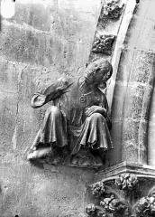 Cathédrale Notre-Dame - Cariatide au dessous de la rose sud, personnage acccroupi et écoutant