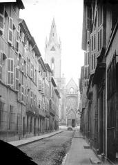 Eglise Saint-Jean-de-Malte - Clocher et portail en arrière-plan d'une rue